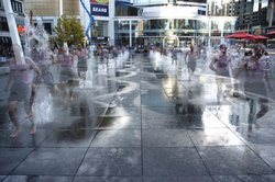 A jogger cools off in the splash fountain that forms the main centerpiece of a flat open space known as Dundas Square at the heart of downtown Toronto. This fountain was designed and built for waterplay, and undergoes strict water quality testing standards. The water is heated using solar energy picked up by special dark colored nonslip granite slabs.