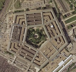 Satellite image of the Pentagon from the , taken April 26, 2002.  The reconstruction of the section damaged on  is visible on the building's west (left) side; the diagonal line is a construction crane