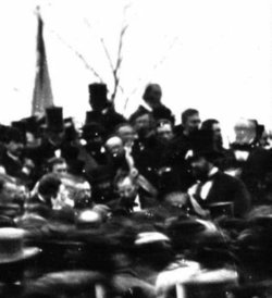 The only known photo of Lincoln at Gettysburg (seated), some three hours before he spoke. To the immediate left (Lincoln's right) is Lincoln's bodyguard, , and beyond the limits of this close-up is Governor  of . Taken about noontime, just after Lincoln arrived, before Edward Everett's arrival. (full view).